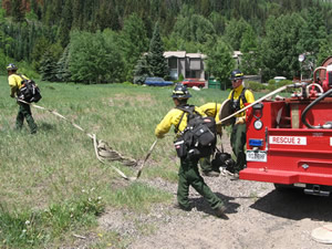 The Vail Fire Department's wildland firefighting team rolls out hoses during training near East Vail's Bighorn Park Monday.