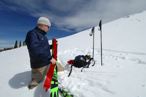 Strapping synthetic seal skins onto a fat pair of telemark skies isn�t always easy, and most backcountry skiers will chose a skinnier ski for this kind of trip. Here the author rigs a set of ropes to his skins to help keep them fastened to the wide base of the ski.